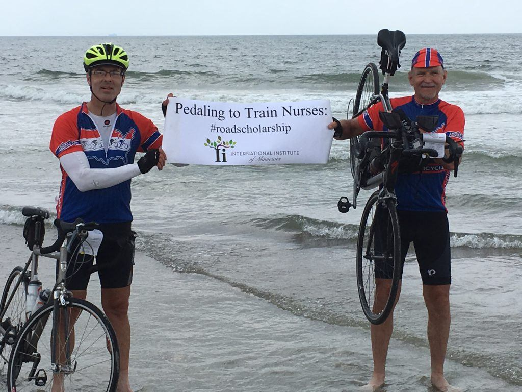 "Jeff at the beach a sign reading ""pedaling to train nurses"""