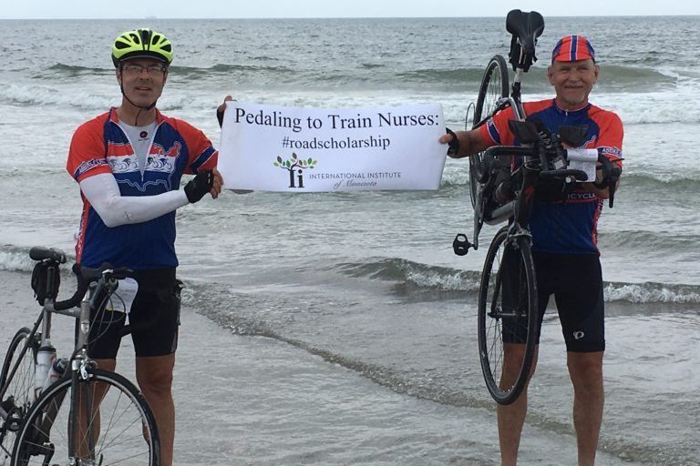 """Jeff at the beach a sign reading """"pedaling to train nurses"""""""