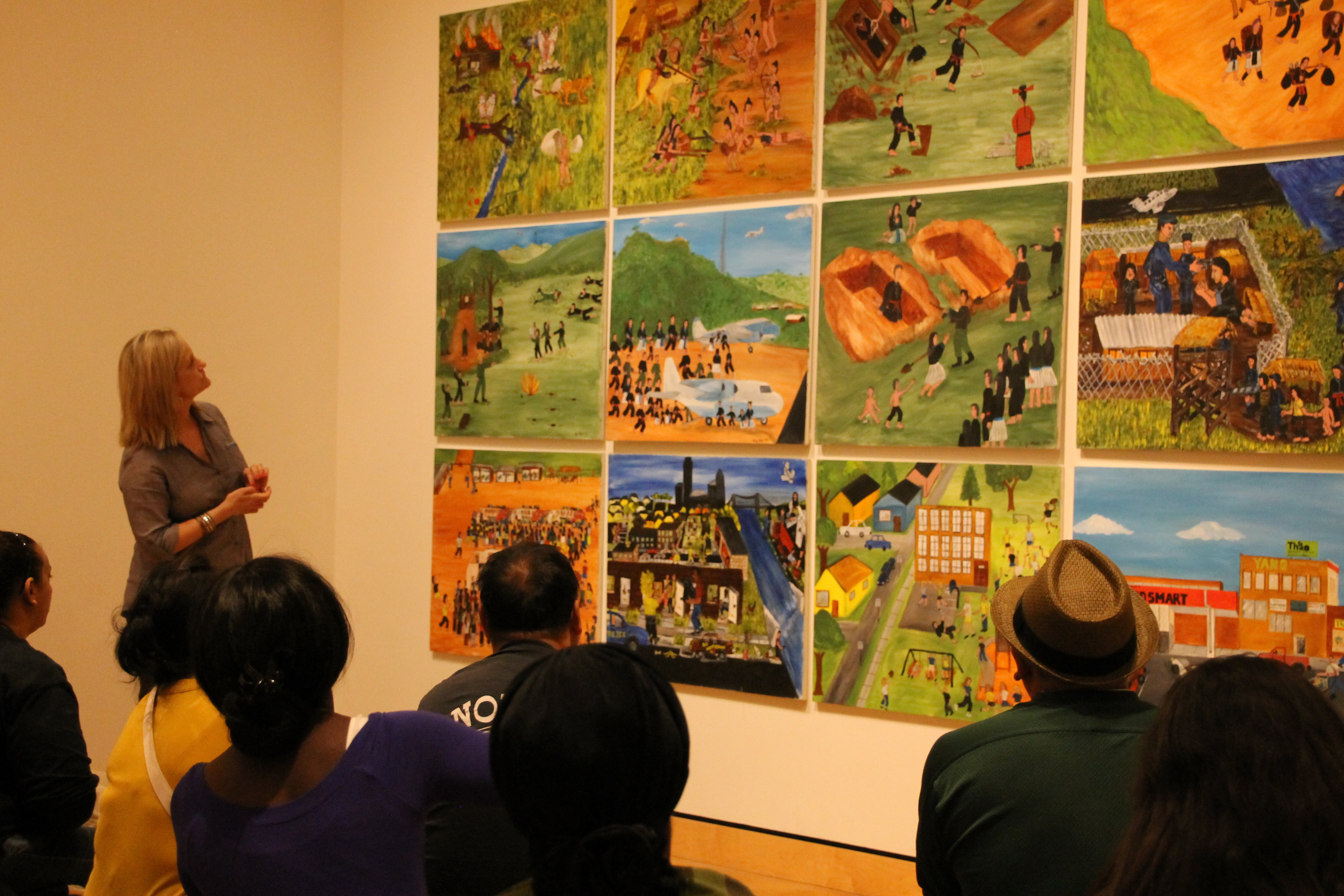 Students looking at Hmong art hanging in Mia