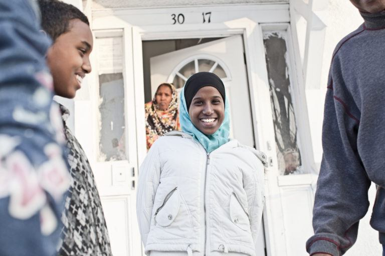 Somali refugee family outside of their home