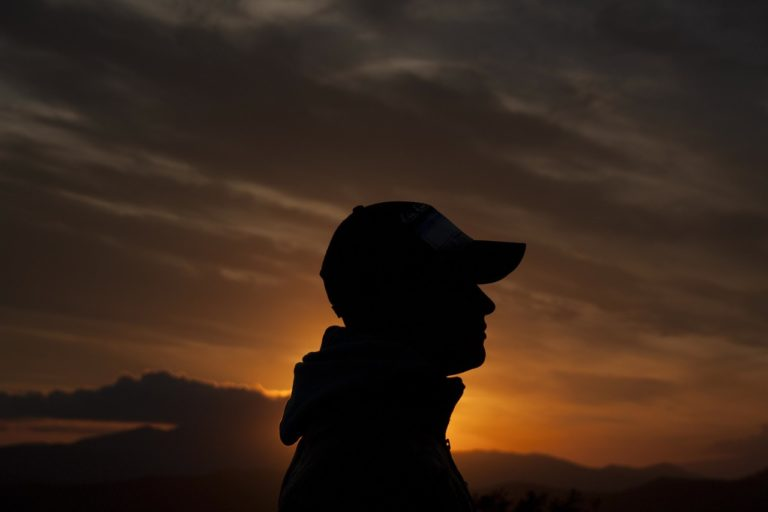 Silhouette of person with cap on at sunset