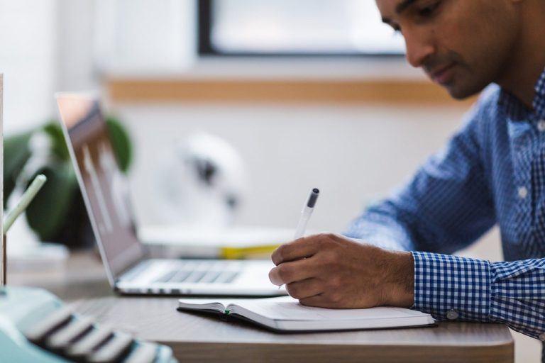 Man writing in a notebook near a computer