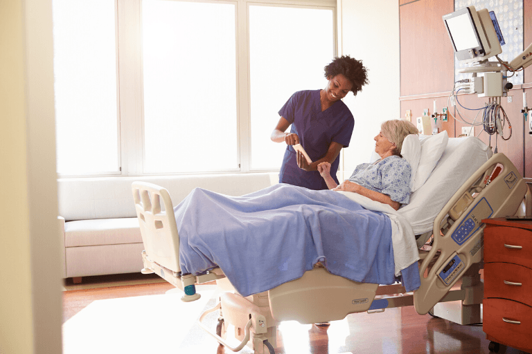 A medical professional assists an elderly woman in a hospital bed