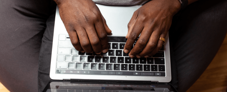 A person's hands on laptop keyboard