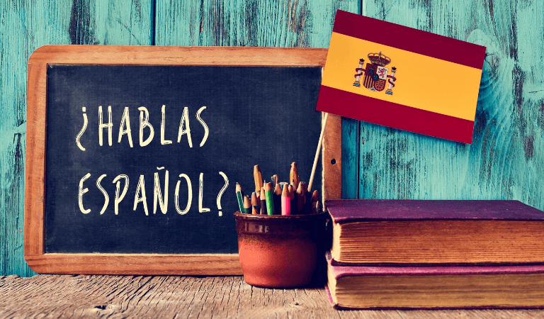 Chalkboard with Hablas Espanol? written, next to Spanish flag, pencils and books