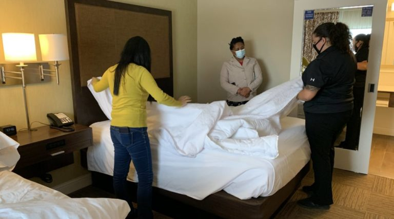 Housekeeping students practice making bed in hotel room