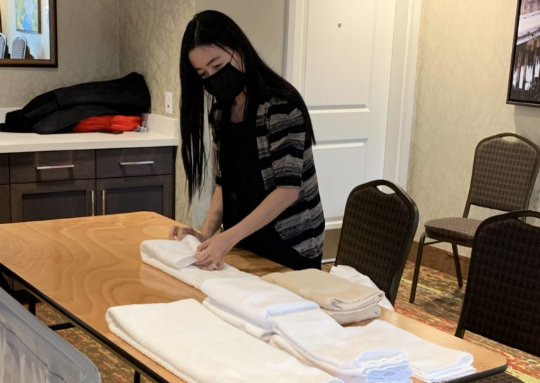 Housekeeping student practices folding hotel towels